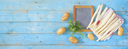 Fresh asparagus, black board, potatoes and parsley Stock Photos