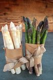 Fresh asparagus bunched. Fresh green and white asparagus bunched on a slate plate in front of a rustic wooden background vertical royalty free stock photo