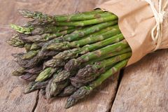 Fresh asparagus in a paper bag on wooden table Stock Image