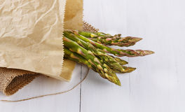 Fresh asparagus on a rustic wooden background. Bunch of fresh asparagus in a paper bag on a white wooden background stock image
