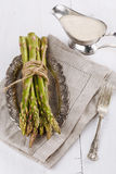 Fresh asparagus on a rustic wooden background. Bunch of fresh asparagus on a vintage silver plate and sauce on a white wooden background stock photos