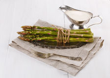 Fresh asparagus on a rustic wooden background. Bunch of fresh asparagus on a vintage silver plate and sauce on a white wooden background stock images