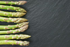Fresh asparagus on slate platter. Fresh green asparagus from market on a black slate platter Stock Image