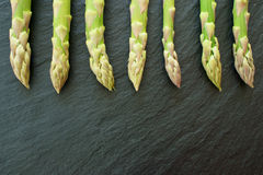 Fresh asparagus on slate platter. Fresh green asparagus from market on a black slate platter Stock Photo