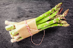 Fresh asparagus spears tied with brown paper Stock Photo