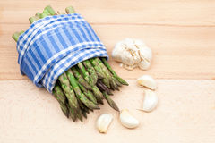 Fresh asparagus stems in a textile napkin and garlic Stock Photos