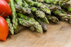 Fresh asparagus and tomatos stock images