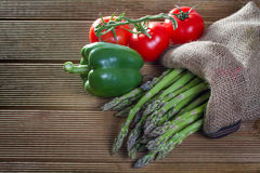 Fresh asparagus with vegetables. On a wooden background Royalty Free Stock Photography