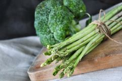 Fresh Asparagus on Wooden Cutting Board. With broccoli on background Royalty Free Stock Images
