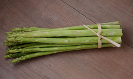 Fresh asparagus on wooden table. Bunch of fresh asparagus on wooden table Stock Photos