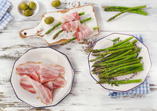 Fresh asparagus wrapped in bacon on a wooden table. Royalty Free Stock Image
