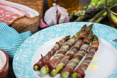 Fresh asparagus wrapped in crispy bacon or pancetta Stock Images