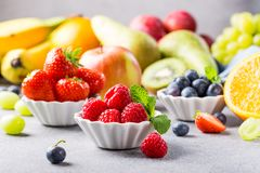 Fresh assorted fruits and berries. On light gray background. Colorful clean and healthy eating. Detox food Royalty Free Stock Photos