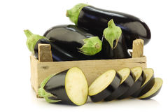 Fresh aubergines and a cut one Royalty Free Stock Photos