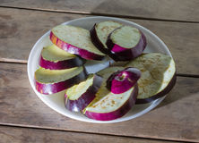 Fresh aubergines in the plate. Fresh aubergines sliced on a white plate on wooden table royalty free stock image