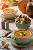 Pumpkin cream soup with fried croutons and seeds vertical side view stock photos