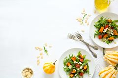 Fresh autumn salad with baked pumpkin, arugula, cheese and seeds on white table cloth. Space for copy stock image
