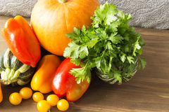 Fresh autumn vegetables. Pumpkin, zucchini, pepper and parsley on a wooden background Royalty Free Stock Photos