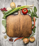 Fresh autumn  and vegetables seasonings and hearbs around a wooden cutting board on bright, rustic wood background top view Royalty Free Stock Photography