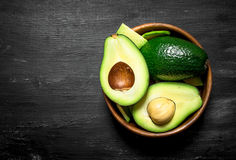 Fresh avocado in a bowl. On black wooden background. Royalty Free Stock Images