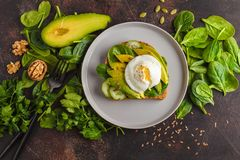 Fresh avocado breakfast with egg poached sandwich. Green salad a. Fresh avocado breakfast with egg benedict sandwich. Green salad and seeds, healthy vegetarian Royalty Free Stock Photography