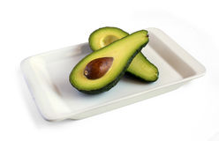 Fresh avocado cut in half on square plate Stock Images