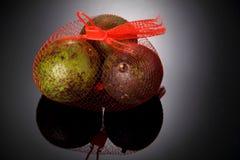 Fresh avocado fruit in plastic net sack. Studio shot high light background Royalty Free Stock Photos