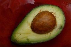 Fresh avocado half on a red ceramic dish Stock Image
