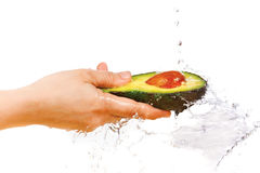 Fresh avocado in hand under flowing water Stock Photo