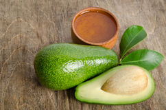 Fresh avocado with a leaves and bowl for oil Royalty Free Stock Images