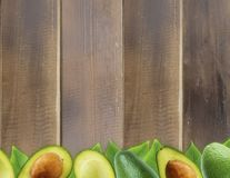 Fresh avocado with leaves on wooden background. Halves of fresh avocado at border of image with copy space for text. Top view. Vegetarian or healthy eating stock photos