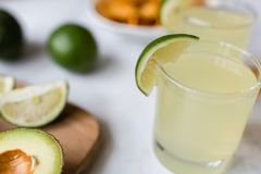 Fresh avocado, lime, drink and nacho chips lying on marble background. Recipe for Cinco de Mayo party. High angle view of two margarita cocktails surrounded by