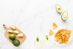 Fresh avocado, lime, drink and nacho chips lying on marble background. Recipe for Cinco de Mayo party. Top view, overhead, flat. High angle view of two margarita