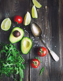 Fresh avocado, lime, tomatoes and arugula with old spoon Stock Image