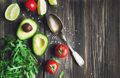 Fresh avocado, lime, tomatoes and arugula with old spoon Royalty Free Stock Photos