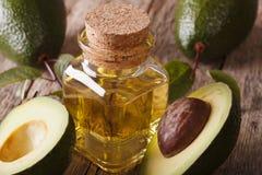 Fresh avocado oil in a glass bottle on a table macro, horizontal Royalty Free Stock Photos