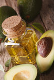 Fresh avocado oil in a glass bottle on a table macro, vertical Stock Images