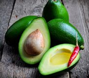 Fresh avocado with olive oil and chili pepper on a wooden background Royalty Free Stock Image