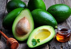 Fresh avocado with olive oil and honey on wooden background Stock Images