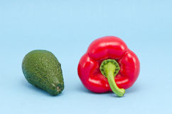 Fresh avocado and red pepper on azure background Royalty Free Stock Photo