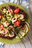 Fresh avocado salad with shrimp and vegetables closeup. vertical Royalty Free Stock Images
