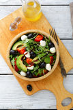 Fresh Avocado Salad with tomatoes, olive, mozzarella and arugula Royalty Free Stock Images