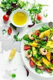Fresh Avocado, Shrimps, Mango salad with lettuce green mix, cherry tomatoes, herbs and olive oil, lemon dressing. Healthy food stock photography