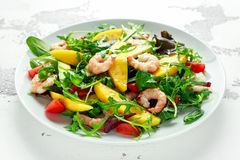 Fresh Avocado, Shrimps, Mango salad with lettuce green mix, cherry tomatoes, herbs and olive oil, lemon dressing. Healthy food royalty free stock images