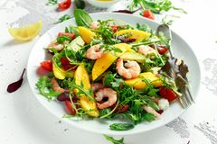 Fresh Avocado, Shrimps, Mango salad with lettuce green mix, cherry tomatoes, herbs and olive oil, lemon dressing. Healthy food royalty free stock image