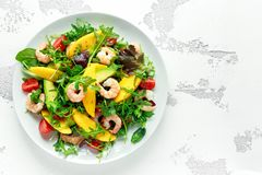 Fresh Avocado, Shrimps, Mango salad with lettuce green mix, cherry tomatoes, herbs and olive oil, lemon dressing. Healthy food stock photos