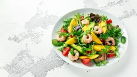 Fresh Avocado, Shrimps, Mango salad with lettuce green mix, cherry tomatoes, herbs and olive oil, lemon dressing. Healthy food royalty free stock photo