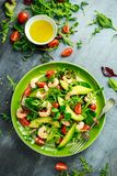 Fresh Avocado, shrimps salad with lettuce green mix, cherry tomatoes, herbs and olive oil, lemon dressing. healthy food.  royalty free stock photography