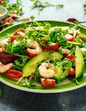 Fresh Avocado, shrimps salad with lettuce green mix, cherry tomatoes, herbs and olive oil, lemon dressing. healthy food.  royalty free stock photos