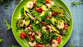 Fresh Avocado, shrimps salad with lettuce green mix, cherry tomatoes, herbs and olive oil, lemon dressing. healthy food.  stock images